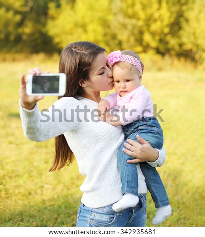 Happy mother and baby taking self-portrait on smartphone in sunny summer day - stock photo
