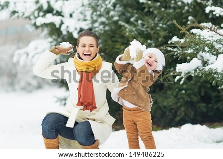 Happy mother and baby throwing snowballs in winter park - stock photo