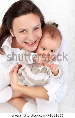 Happy mother and beautiful baby girl sitting on the floor - top view