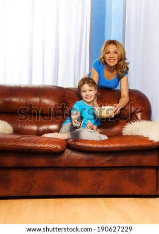 Happy mother and boy watching TV program together - stock photo