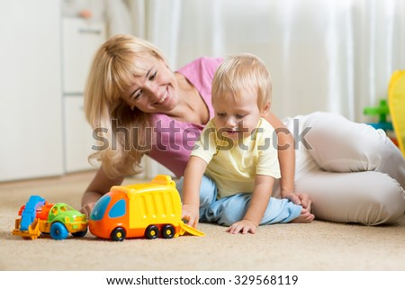 happy mother and child boy play with car toys together at home
