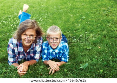 Happy mother and child laying on meadow - stock photo