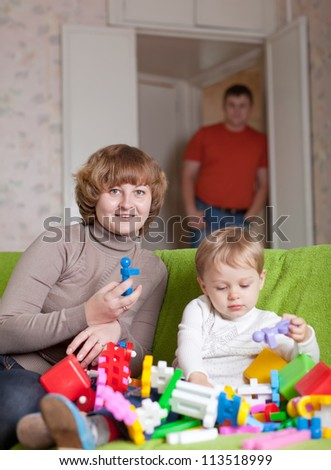 Happy mother and child plays with toys in home. Focus on woman only - stock photo