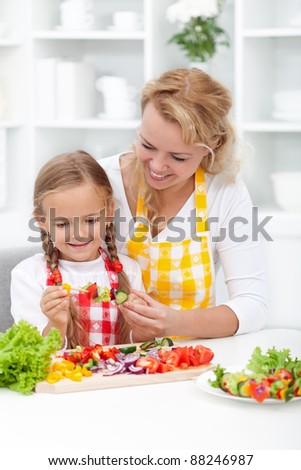 Happy mother and child preparing healthy fresh food - stock photo