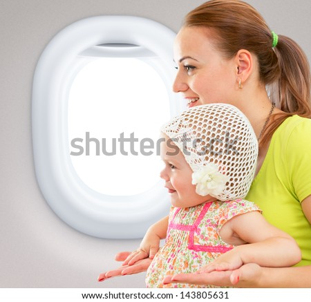 Happy mother and child sitting together in airplane cabin near window - stock photo