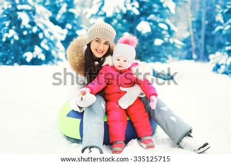 Happy mother and child sitting together on sled in winter snowy day - stock photo