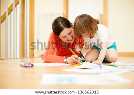 Happy mother and child sketching  on paper at parquet floor - stock photo