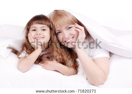 Happy mother and child smiling under the blanket
