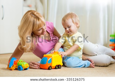 happy mother and child son playing with car toys together at home - stock photo