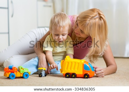 happy mother and child toddler boy playing together at home - stock photo