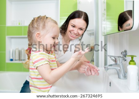 Happy mother and child washing hands with soap together in bathroom - stock photo