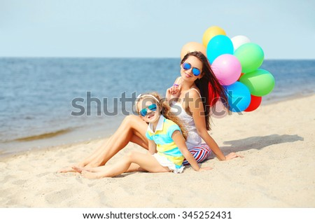 Happy mother and child with colorful balloons on beach near sea - stock photo
