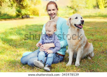 Happy mother and child with Golden Retriever dog on grass in park