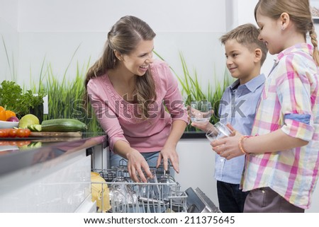 Happy mother and children placing glasses in dishwasher - stock photo