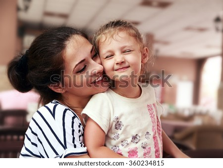 Happy mother and cute enjoying kid girl cuddling with love and closed eyes indoor restoration background  - stock photo