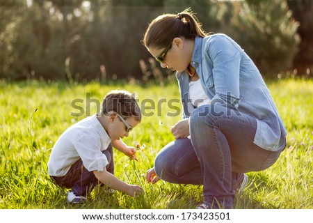 Happy mother and cute son picking a bouquet of flowers in sunny field