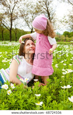 Happy mother and daughter among white flowers - stock photo