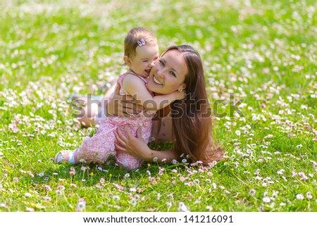 Happy mother and daughter are lying on grass in the park. - stock photo