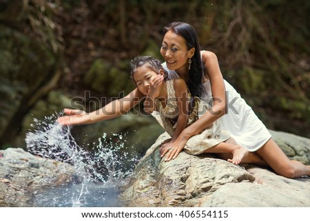 happy mother and daughter asian appearance playing near a waterfall in the mountains