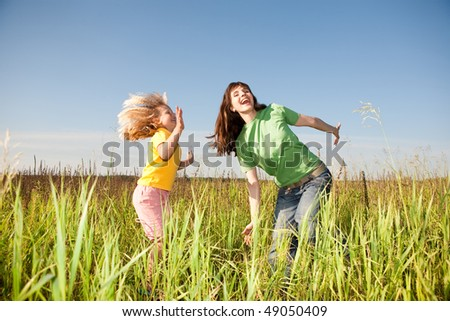 Happy mother and daughter at field - stock photo