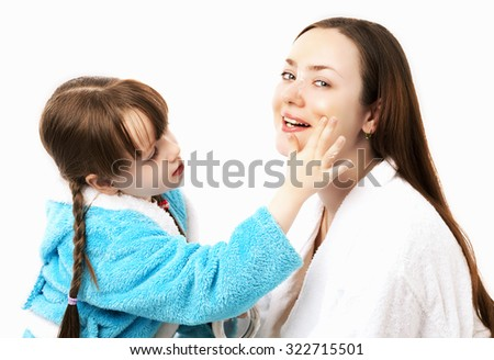 happy mother and daughter at home, daughter applying cream on  her mother's face, isolated against white background - stock photo