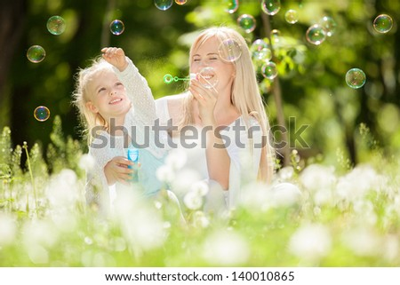 Happy mother and daughter blowing bubbles in the park - stock photo