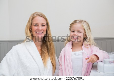 Happy mother and daughter brushing their teeth at home in the bathroom - stock photo