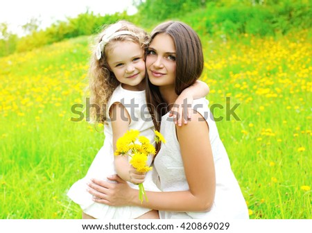 Happy mother and daughter child together with yellow dandelion flowers in summer day - stock photo