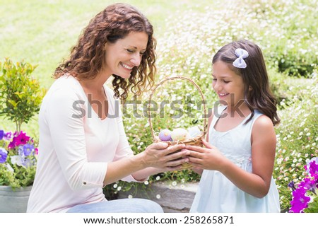 Happy mother and daughter collecting easter eggs in the garden - stock photo
