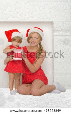 happy mother and daughter dressed as Santa with gift and snow on gray background
