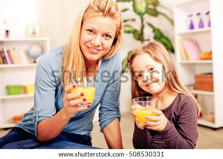 Happy mother and daughter drinking juice