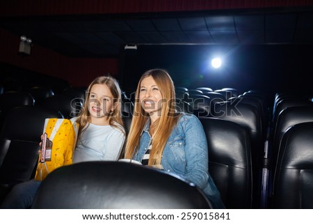 Happy mother and daughter enjoying film in movie theater - stock photo