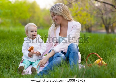 Happy Mother and daughter having a picnic in a park