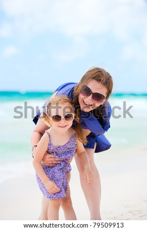 Happy mother and daughter having fun at beach - stock photo