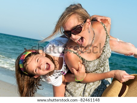 Happy mother and daughter having fun spending time together on a beach - stock photo