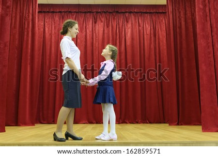 Happy mother and daughter hold hands and look at each other on stage with red curtains. - stock photo