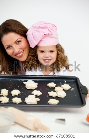Happy mother and daughter holding a plate with biscuits in the kitchen