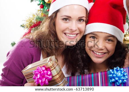 happy mother and daughter holding Christmas gifts - stock photo