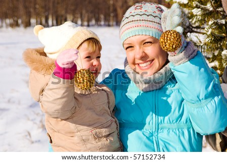 Happy mother and daughter holding xmas decoration in hands - stock photo