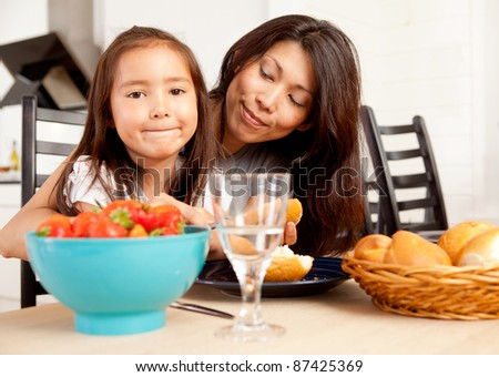 Happy mother and daughter in kitchen eating meal with fresh picked strawberries - stock photo