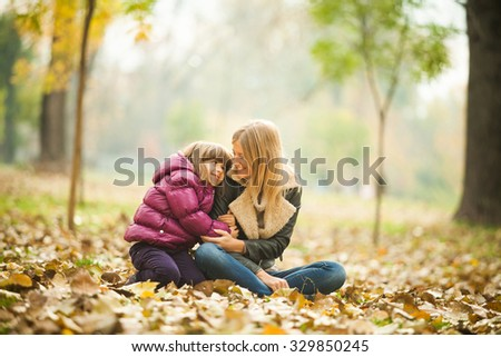 Happy mother and daughter in park in autumn