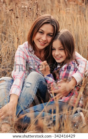 happy mother and daughter in plaid shirts hugs on cozy walk on country sunny field