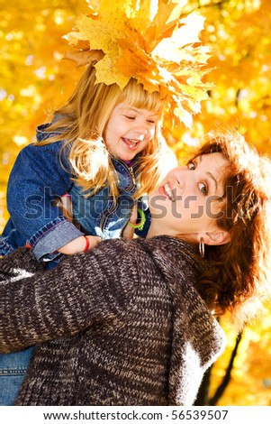 Happy mother and daughter in the autumn park - stock photo
