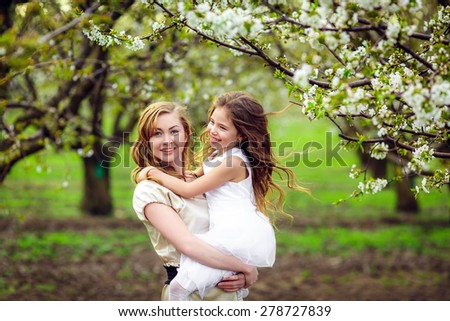 Happy mother and daughter in the flowered garden - stock photo