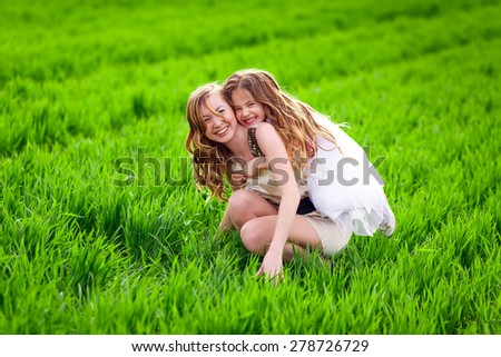 Happy mother and daughter in the meadow