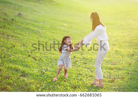 Happy mother and daughter in the meadow on a bright day