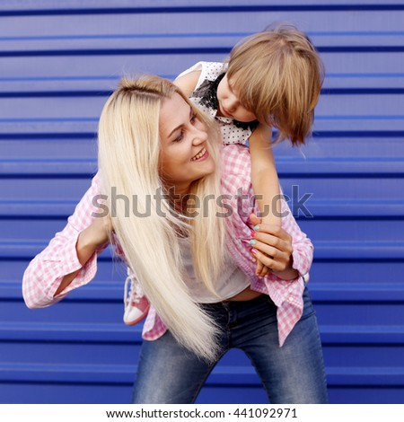 Happy mother and daughter laughing together outdoors. Mother Day. - stock photo