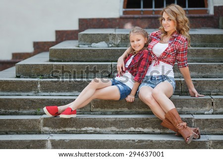 Happy mother and daughter laughing together outdoors. Woman and child in nature. Mother and daughter outdoors. - stock photo