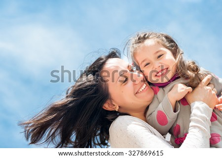 Happy mother and daughter look in the camera and laugh. The picture is photographed from below, the bright blue sky as a background. - stock photo