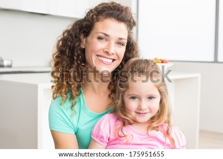 Happy mother and daughter looking at camera at home in kitchen